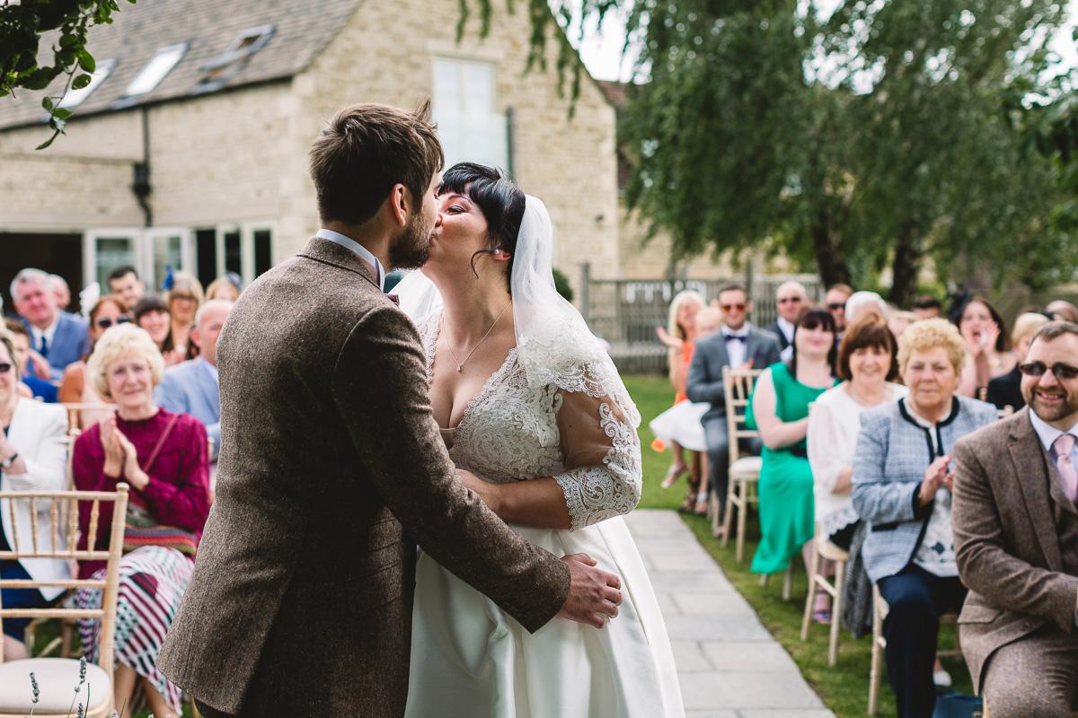 First kiss at fun outdoor hyde barn wedding