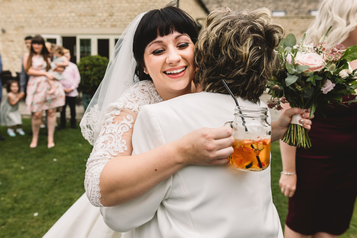 Bride and grandmother hug at summer outdoor wedding in the Cotswolds