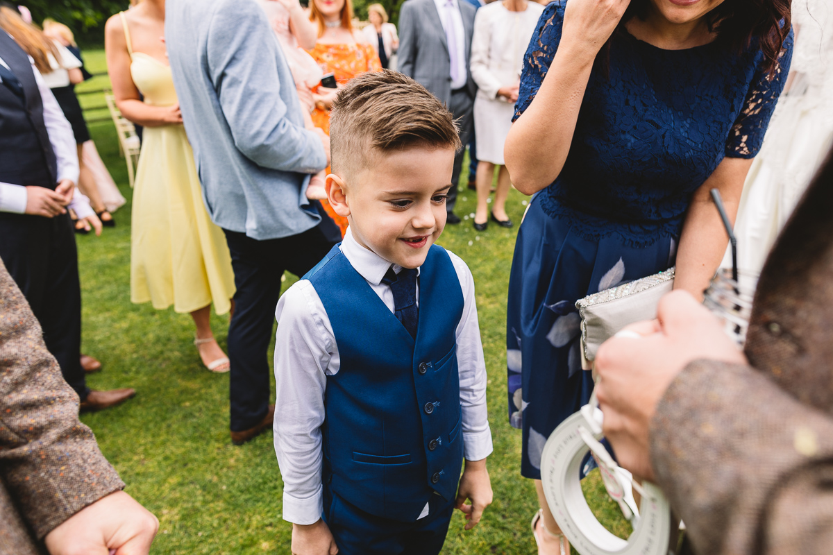 Page boy gives groom horseshoe at Outdoor Hyde Barn Wedding