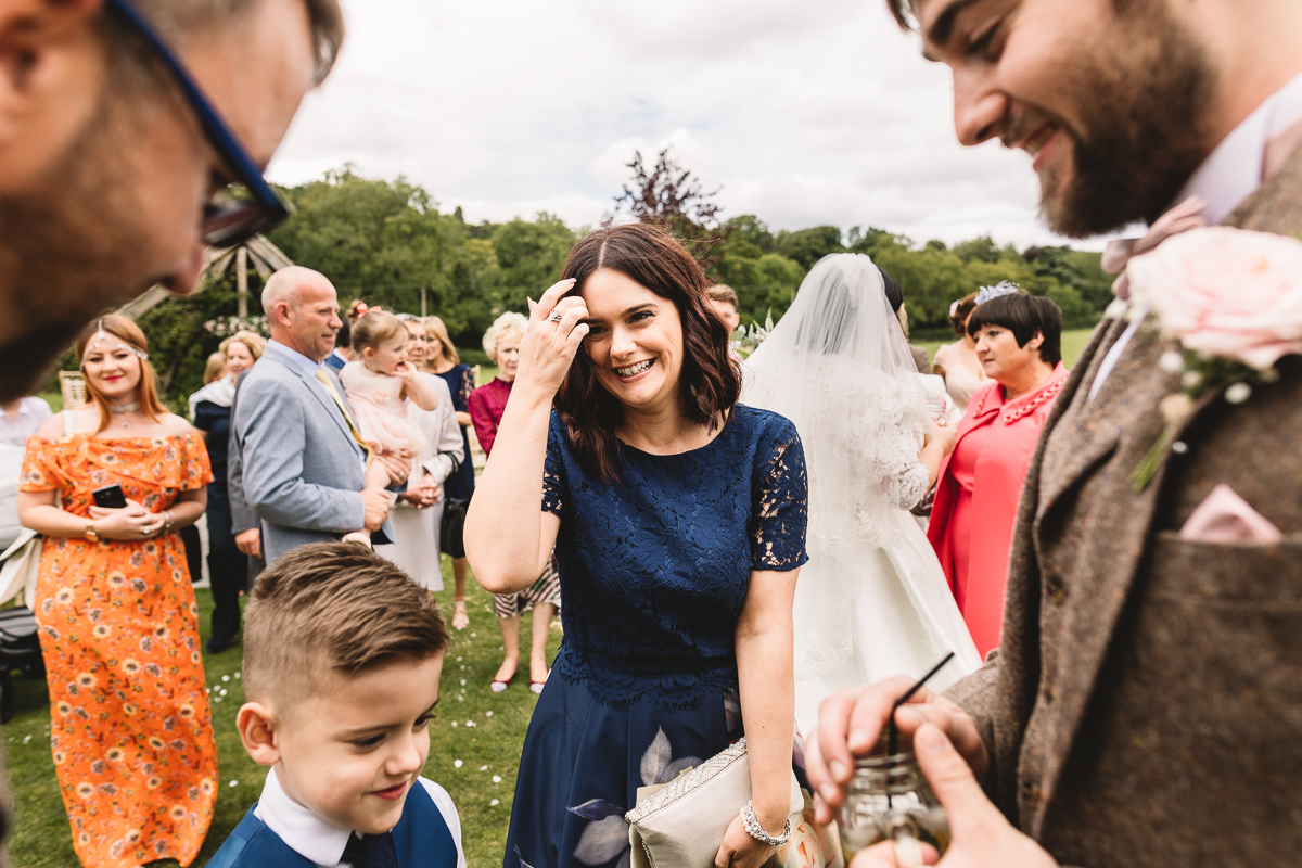 Woman in blue dress smiles after outdoor wedding ceremony at Hyde Barn