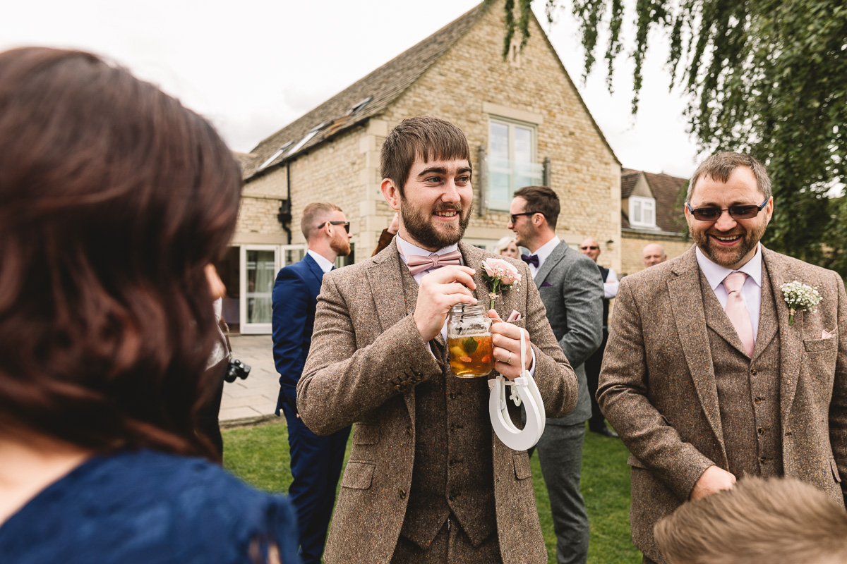 Groom holds horseshoe and drinks pimms at diy outdoor wedding in Cotswolds