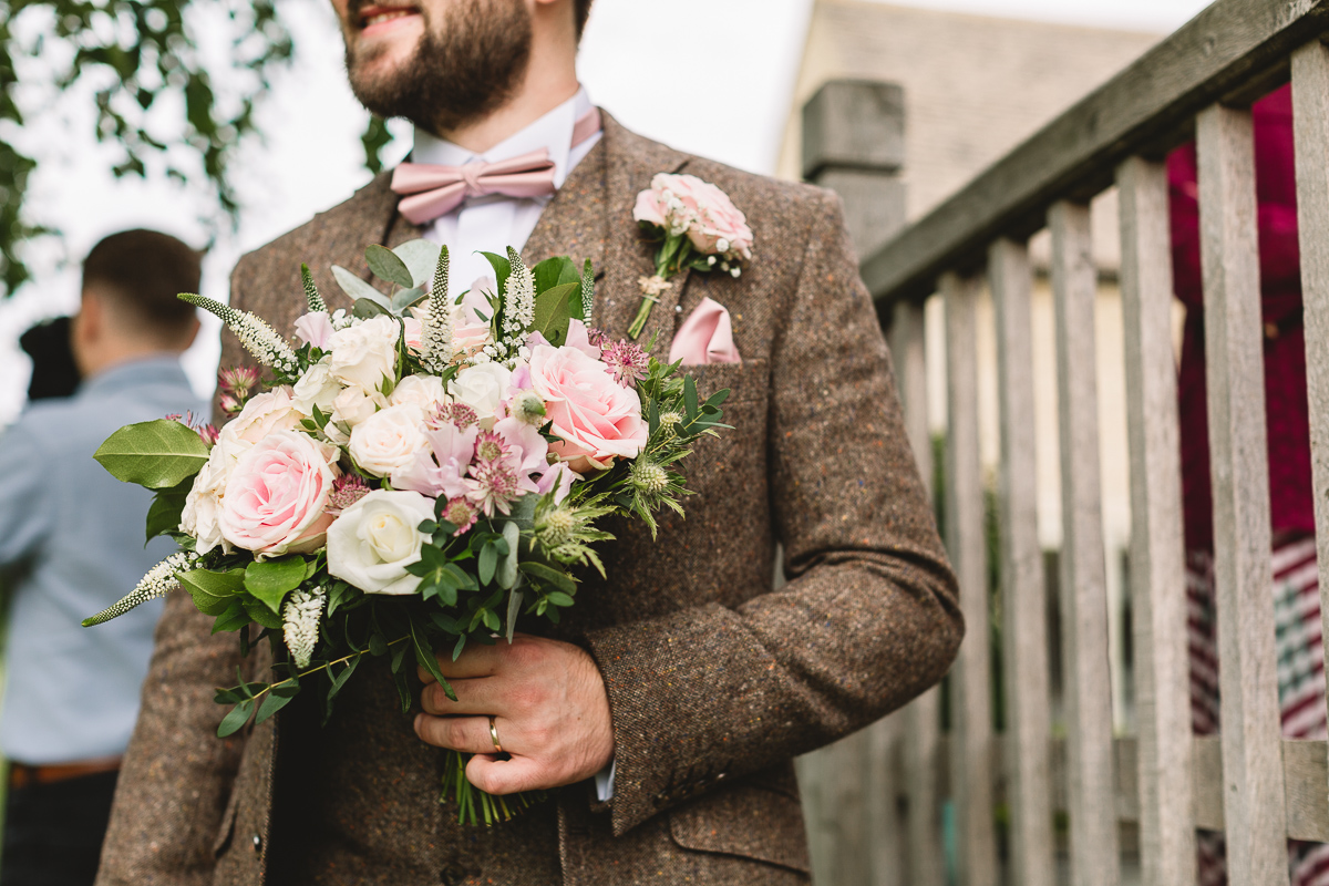 Groom in fun pink bow tie holds onto brides bouquet in the Cotswolds