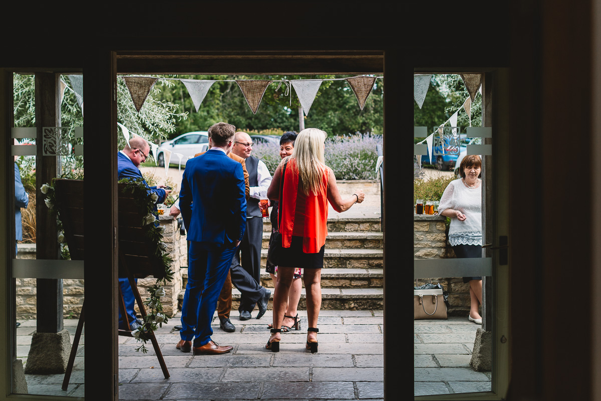 Documentary Wedding Photo of people standing outside at Hyde Barn Weddings