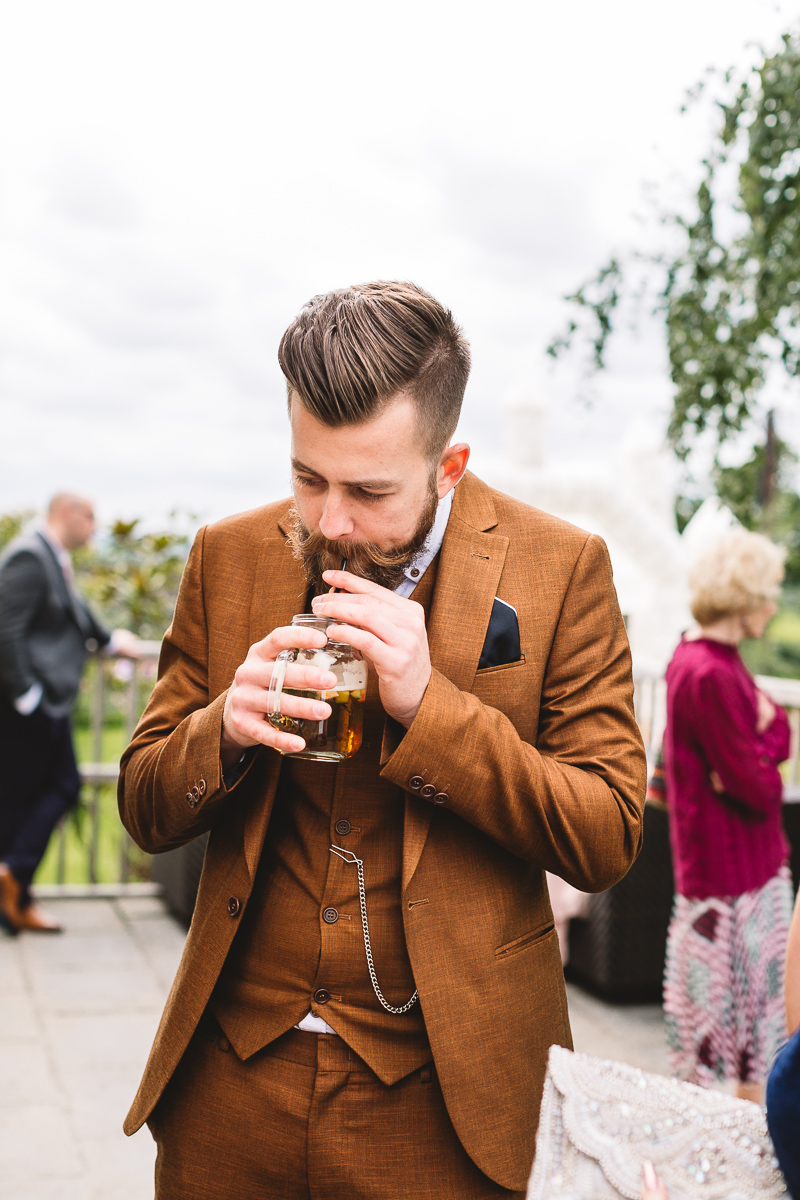 Bearded Guest Drinks Pimms at Hyde Barn Weddings
