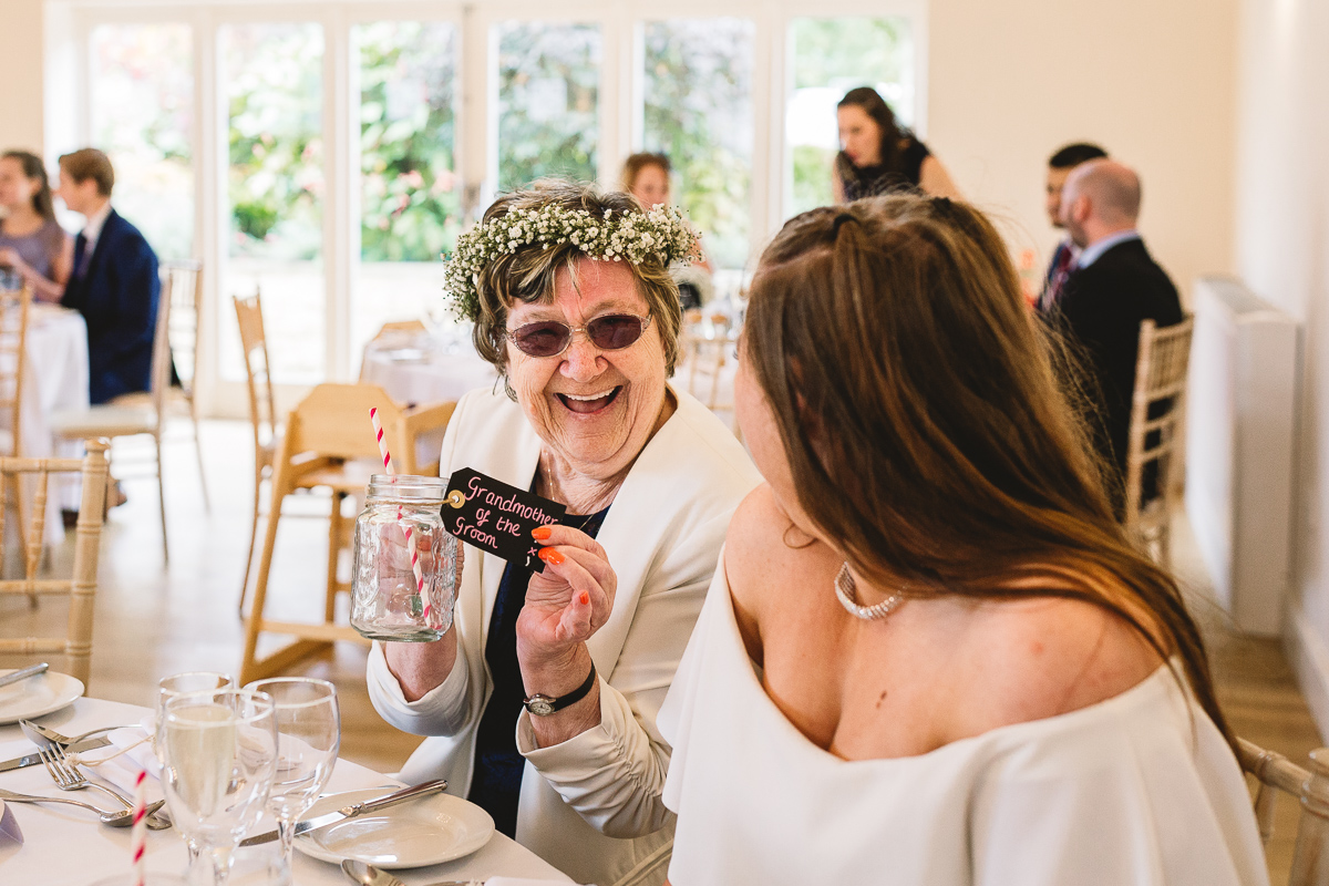 Grandmother with flower crown holds up fun vintage glass tumbler with her name card