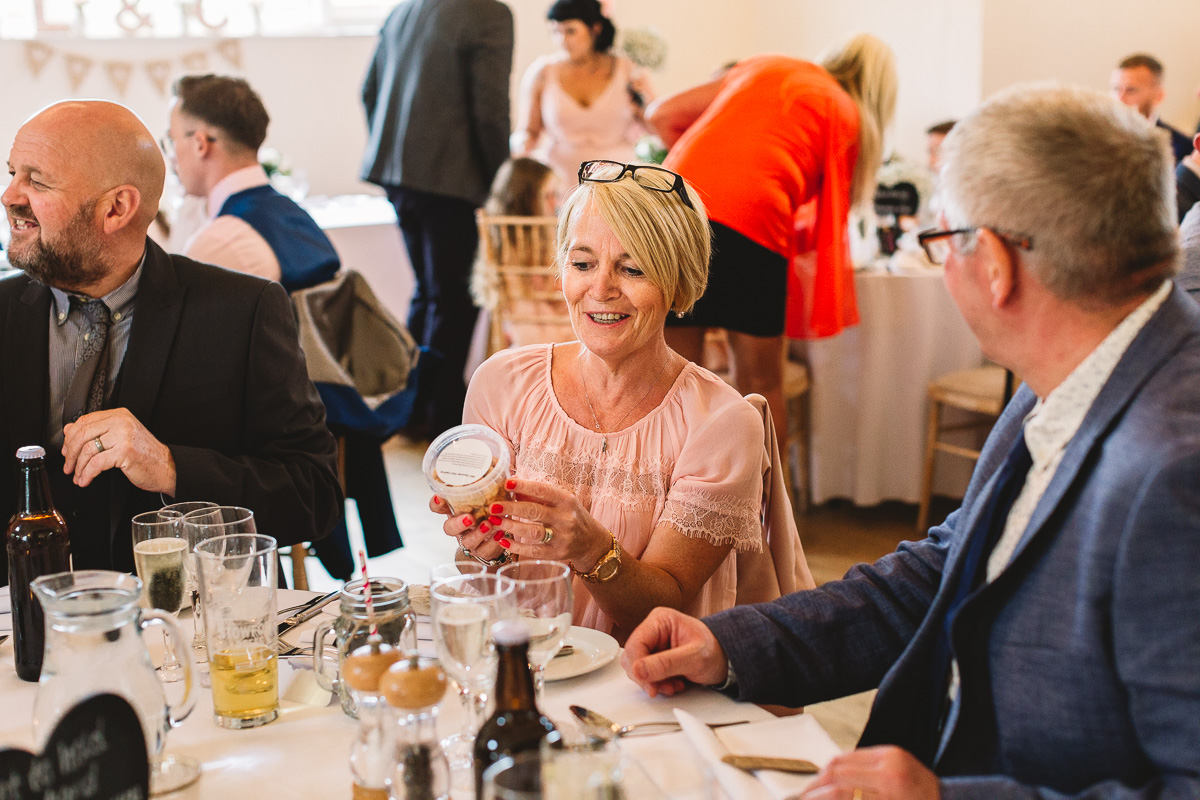 Woman in pink holds wedding favour inside the rustic Hyde Barn