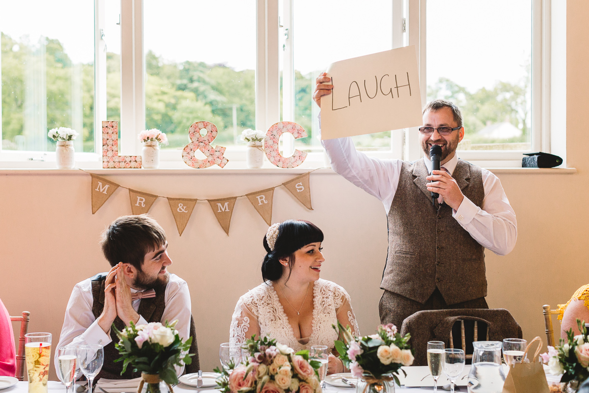 Fun Wedding at Hyde Barn with Dad holding up laugh card during funny speech