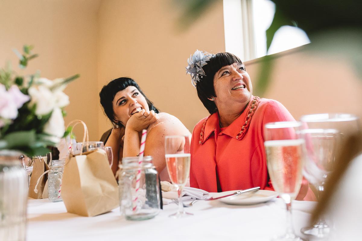 Mum in pink coat smiles at fun Costwolds Wedding