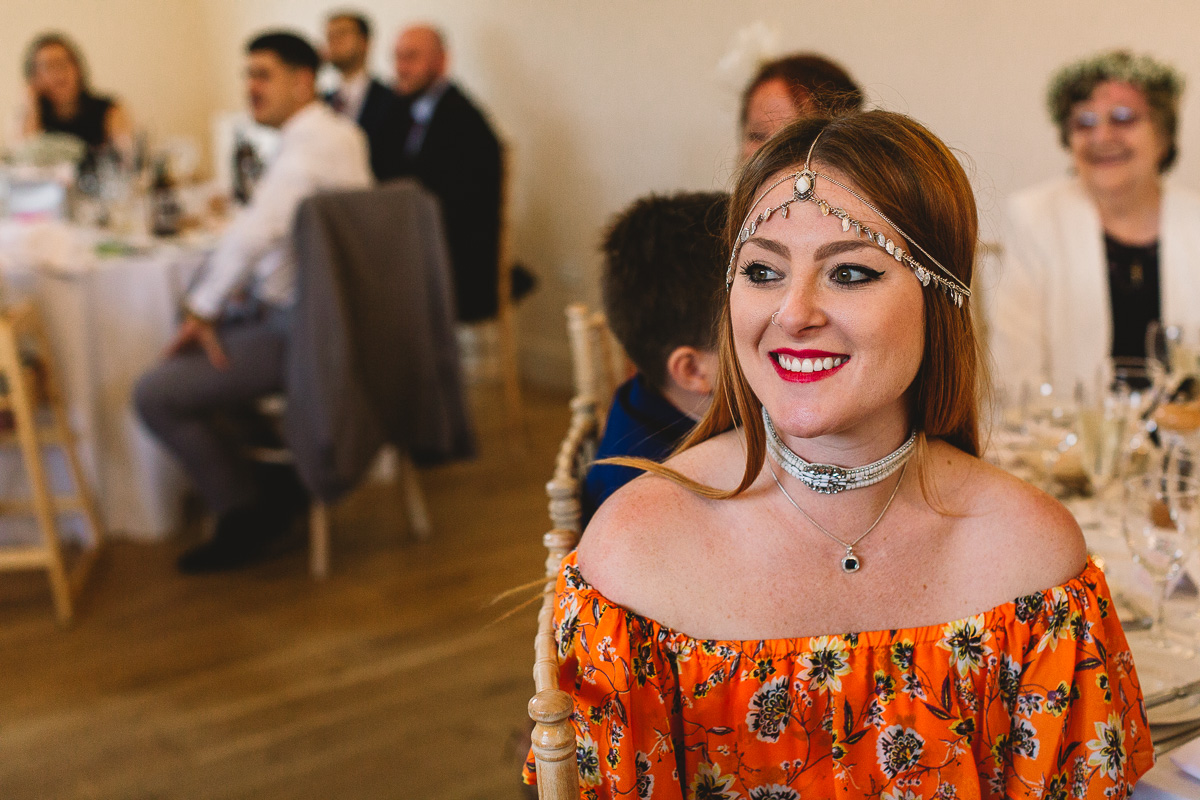 Alternative guest in hippy floral style dress smiles | Cotswolds Hyde Barn Wedding