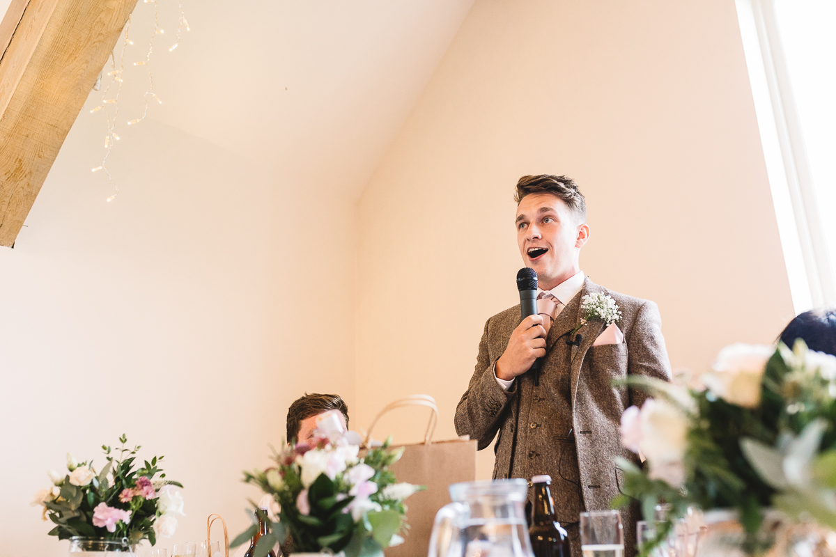 Portrait of Best Man during wedding speech he's giving at Rustic Hyde Barn