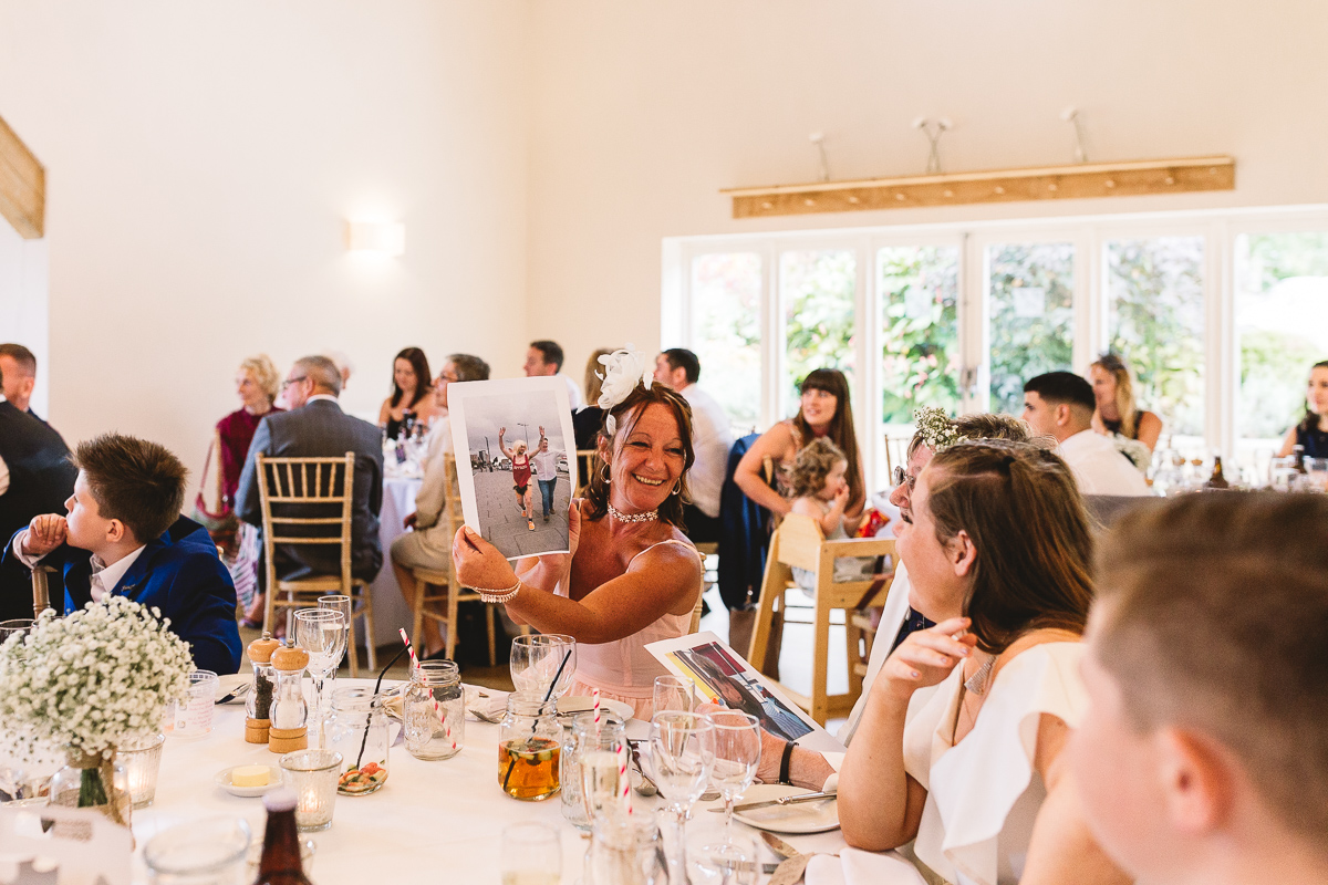 Lady holds out fun photo of groom on stag party during wedding speeches