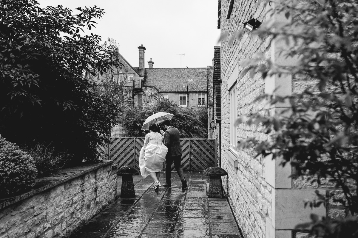 Couple has fun running in the rain with umbrella at cotswolds hyde barn wedding