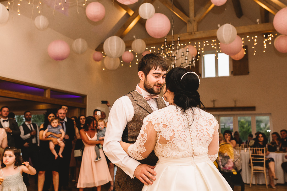 Groom looks at bride happily in first dance at Cotswolds wedding