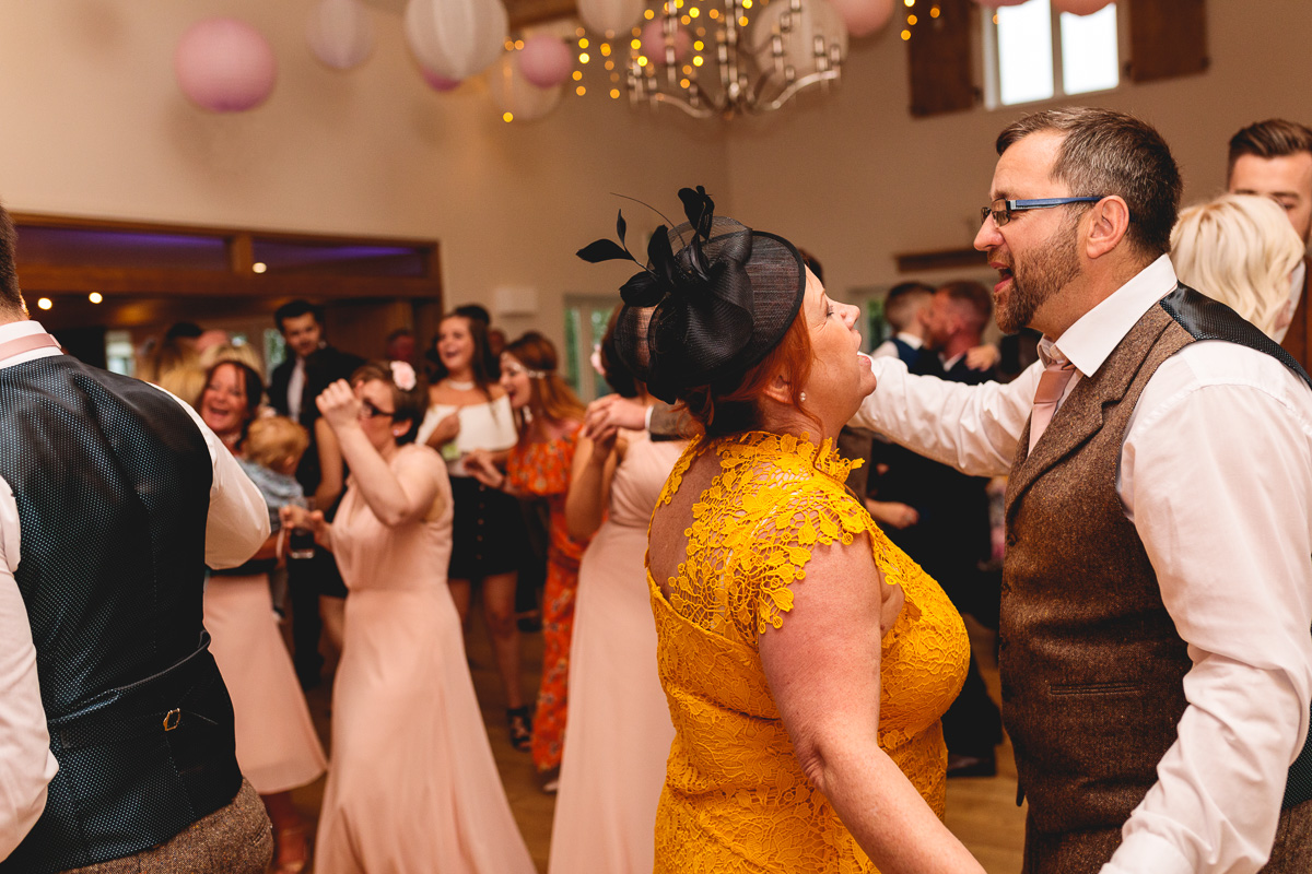 Mother and father dance and have fun at summer wedding in cotswolds