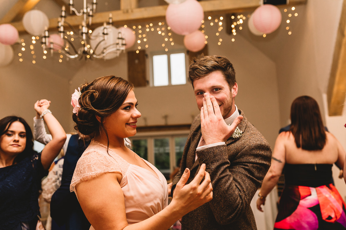 Groomsman pulls a funny amusing face at Rustic Hyde Barn Wedding