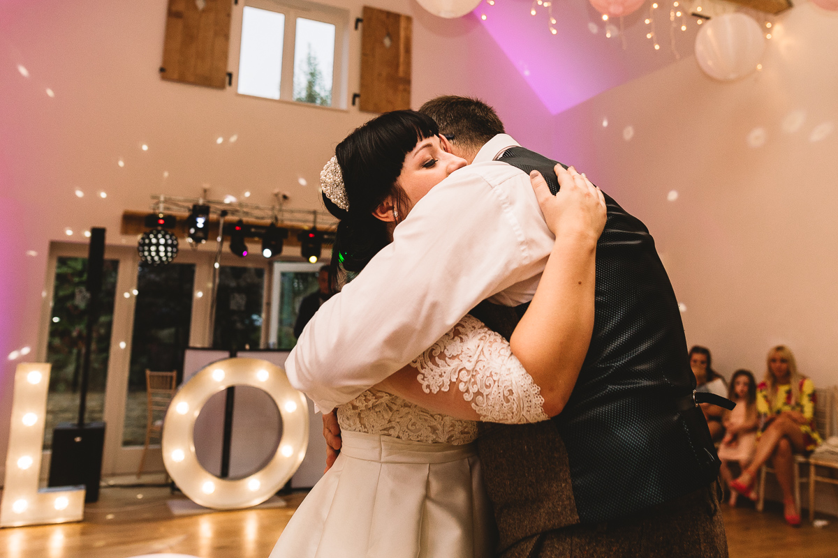 Photo of father and bride embrace in natural moment