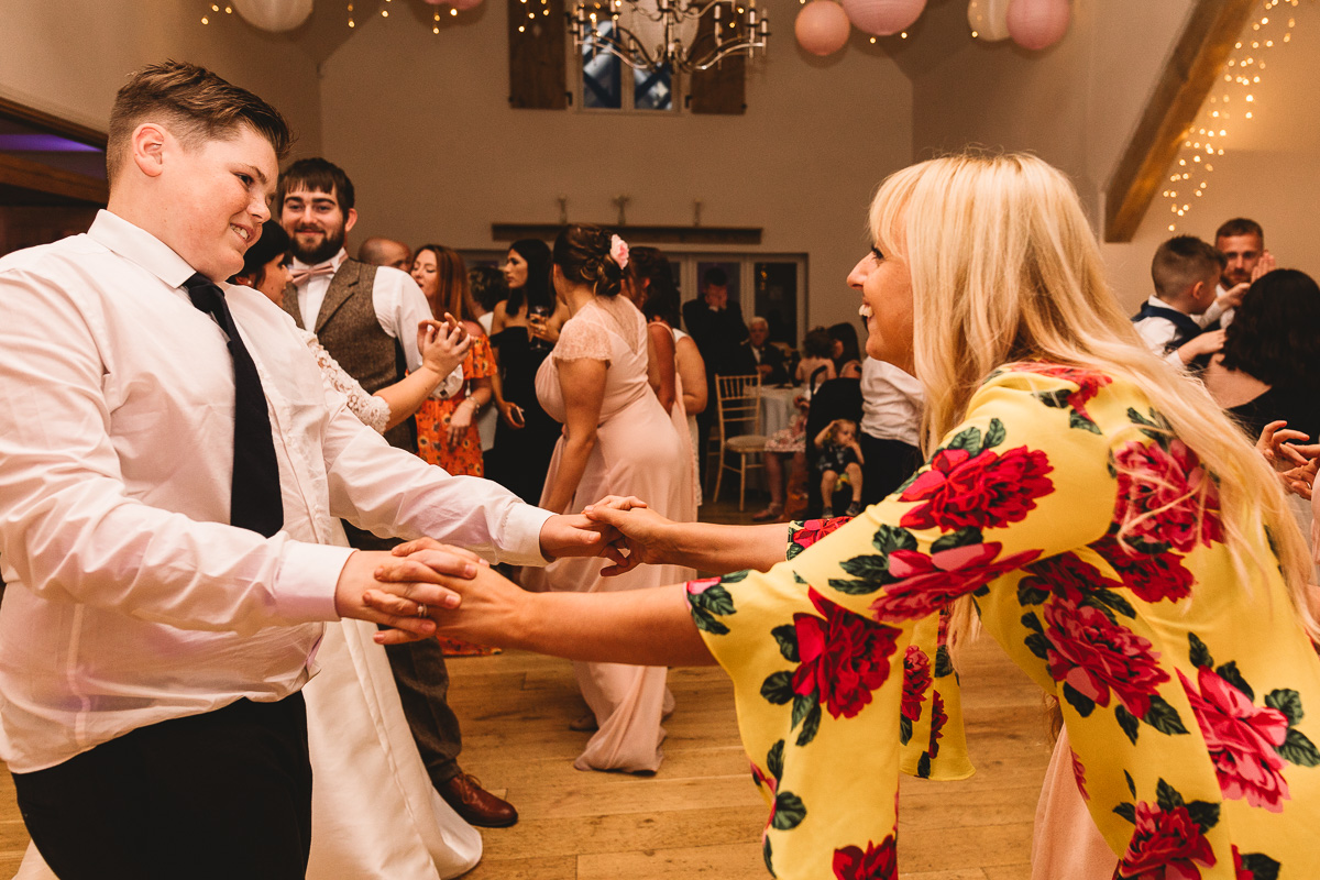 Fun and colourful photo of people dancing at Cotswolds wedding