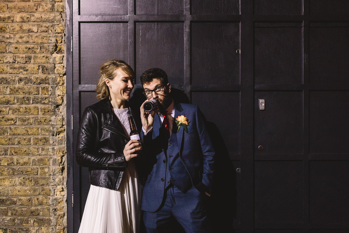 Cool couple side by side against urban black doors and bricks drinking bespoke craft beer at their Fun Winter Clapton Country Club Wedding