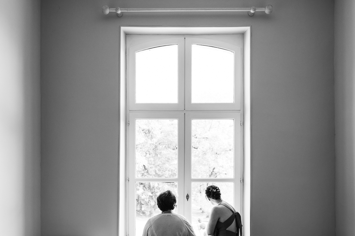 Documentary photo of bridal party looking out of chateau windows