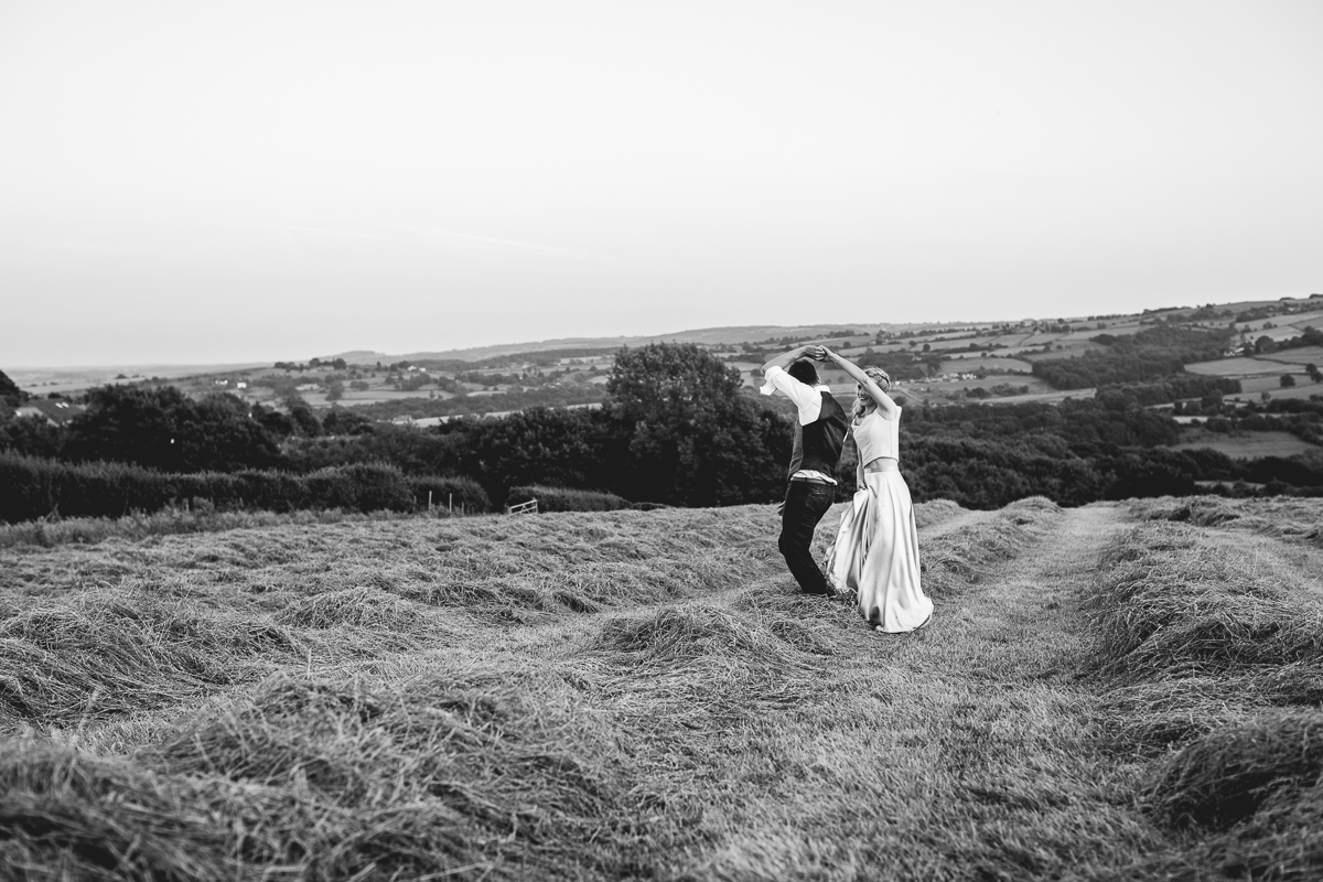 Black and white photo of bride and groom who are dancing in a field at a DIY festival wedding in Sheffield. The bride is wearing an untraditional two piece wedding dress and the groom is casual with white shirt and waistcoat. The bride is twirling the groom under him.