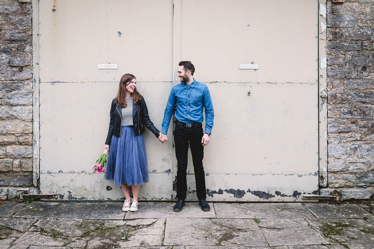 Bride and groom holding hands against metal shutter doors on a barn in Warwickshire. The bride wears an untraditional purple tulle skirt, striped top, black leather jacket and glittery trainers and has mid to long brown hair. The groom has a dark beard and is wearing a blue denim shirt, black jeans and black doc martins. Bride is holding a bouquet made of tulips.