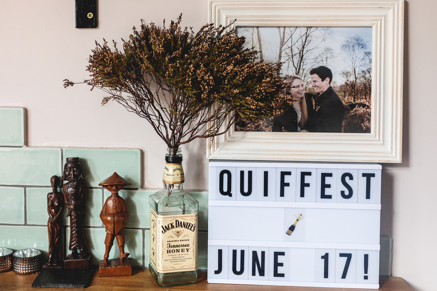 Rustic flowers in whiskey bottle with a light up cinema sign that says Quiffest June 17 with a photo in frame of a fun couple on engagement photo shoot in woods in sheffield