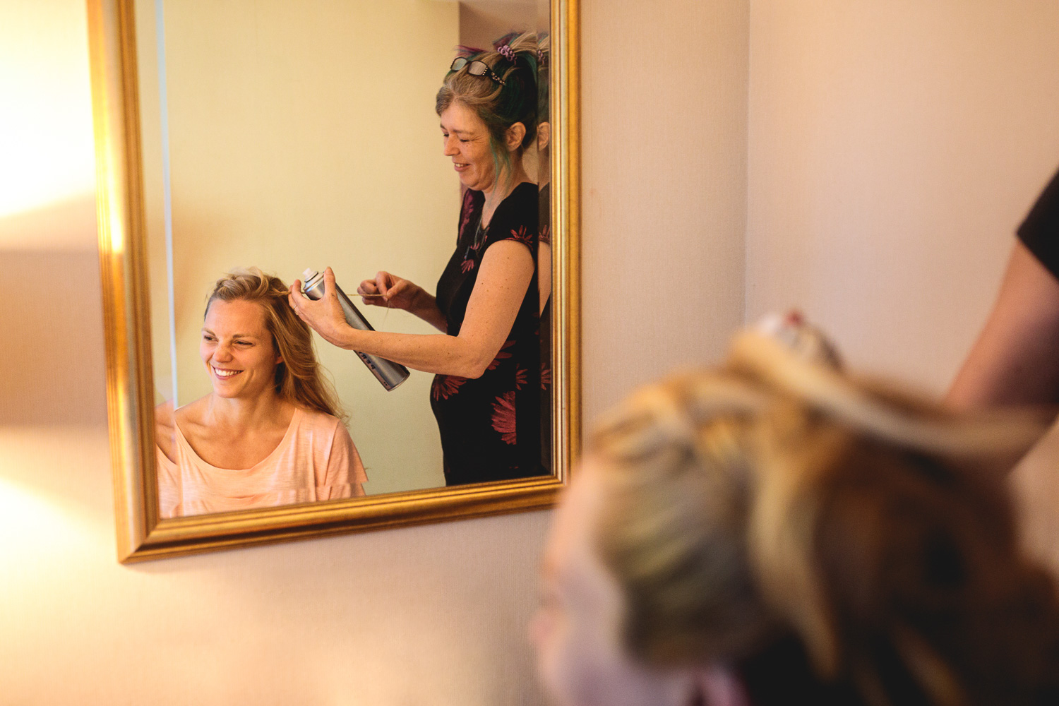Bride in Sheffield having her hair platted by hairdresser with multicoloured hair and laughing