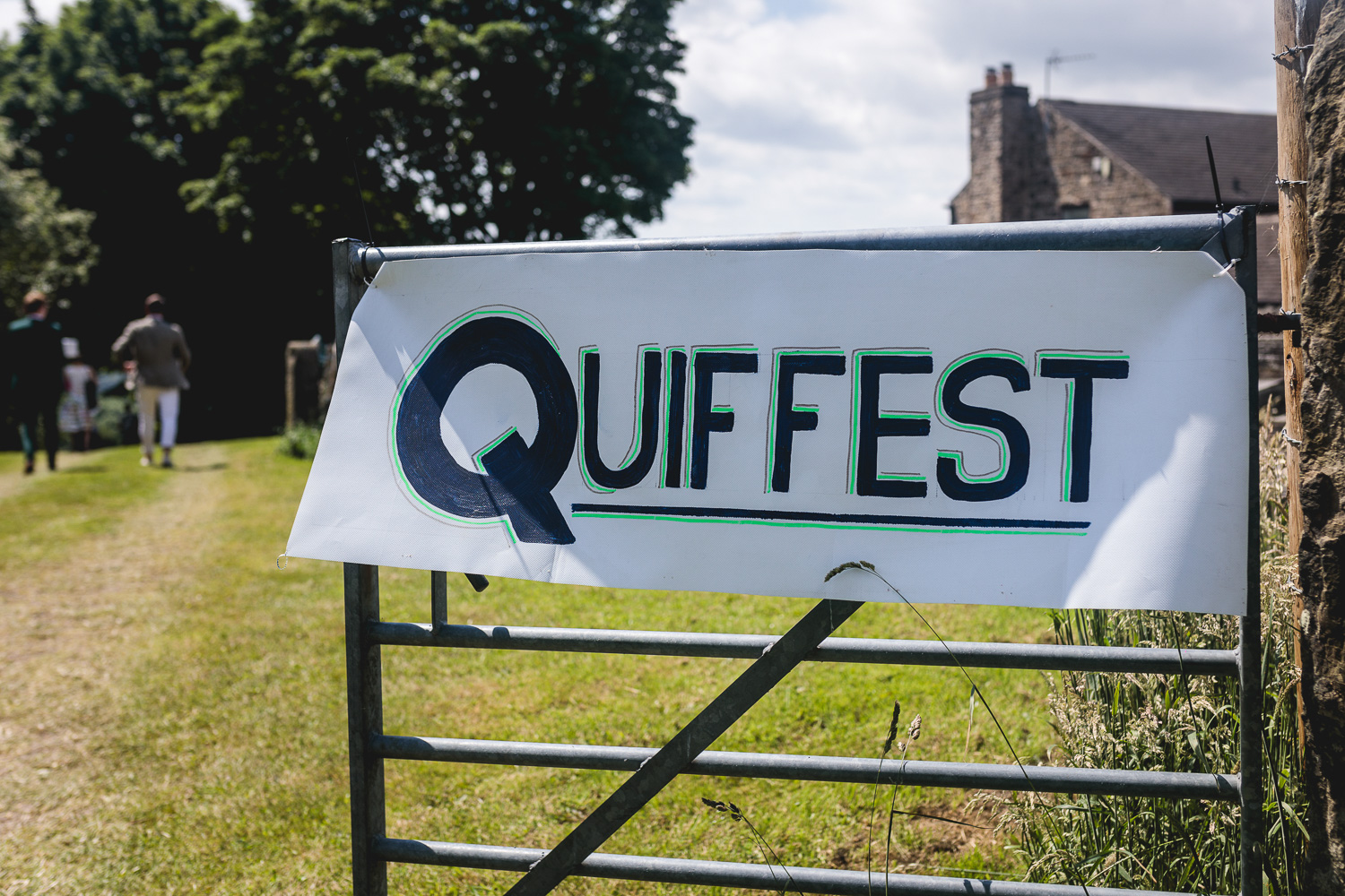 Hand Painted Festival wedding sign that reads 'Quiffest' attached to gate at entrance to field for wedding in sheffield