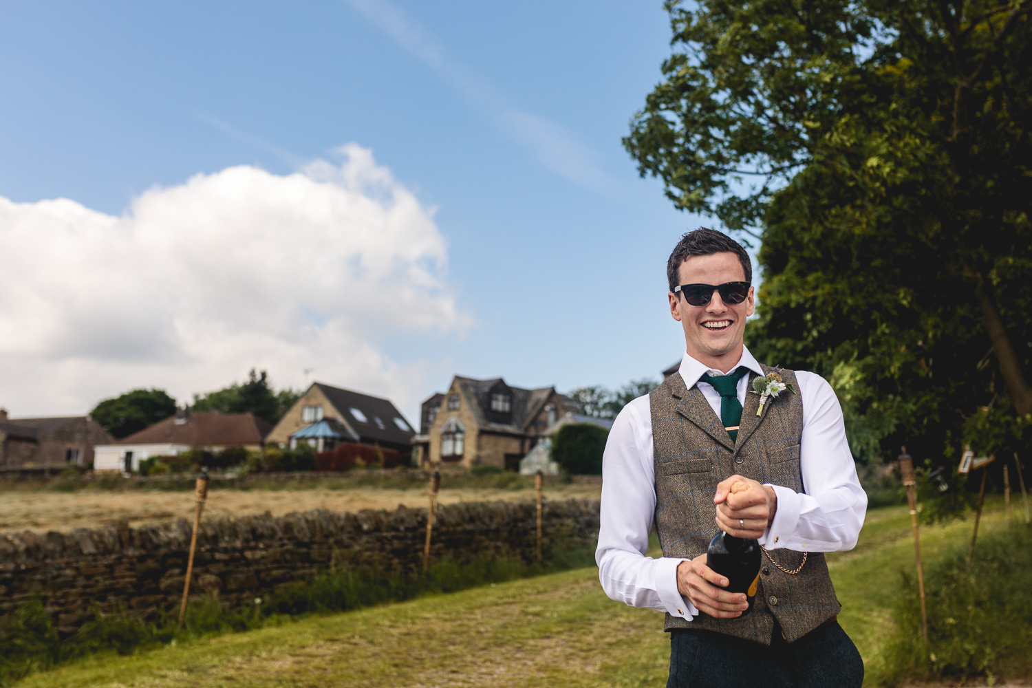 Fun groom wearing sunglasses and rustic tweed suit in outdoor field in sheffield popping a bottle of prosecco