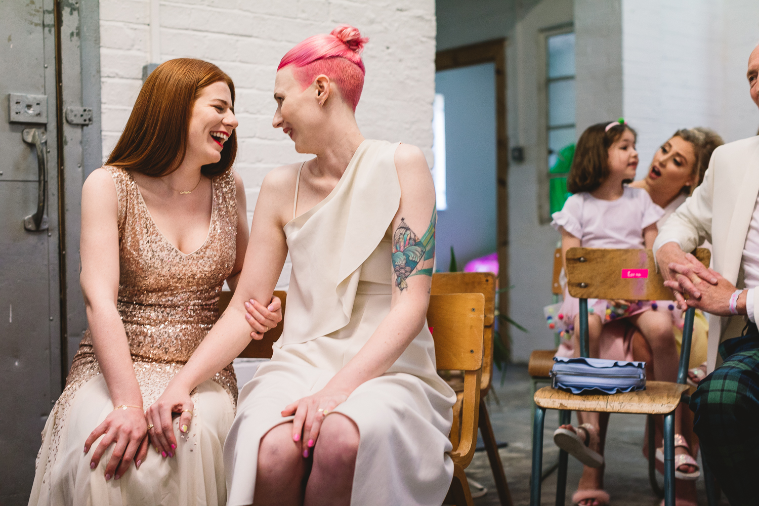 Two brides, one with tattoos and pink hair, the other wearing gold dress, smiling and laughing sat down arm in arm during their fun hackney wedding ceremony