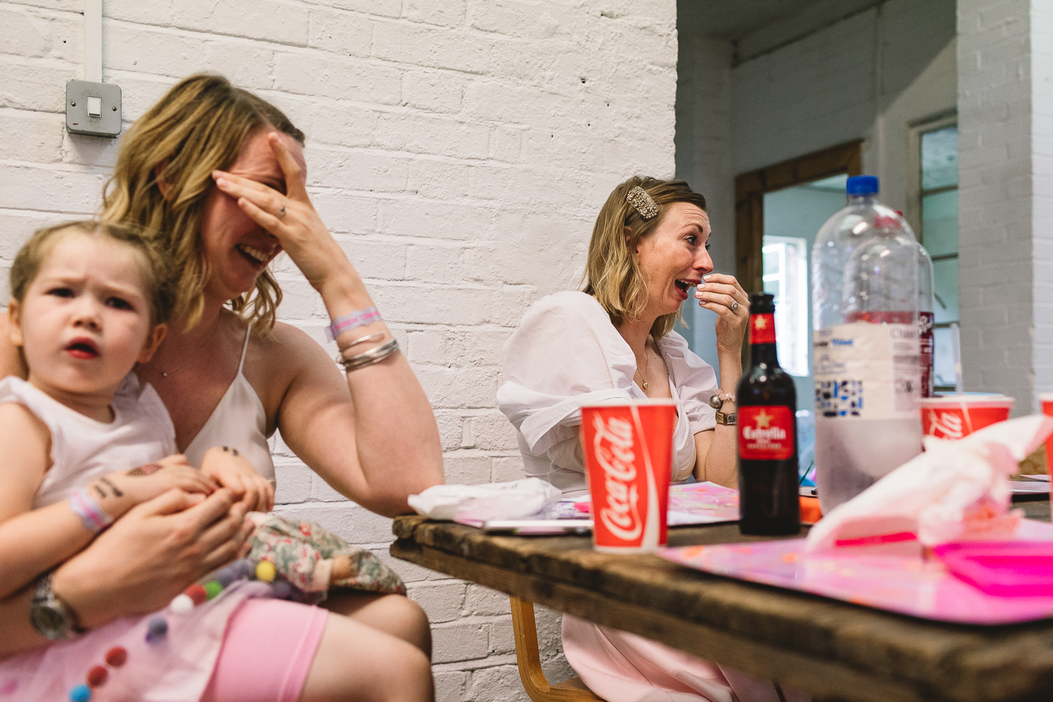 Bridesmaids laughing during wedding speech at fun and colourful Hackney Warehouse wedding in London
