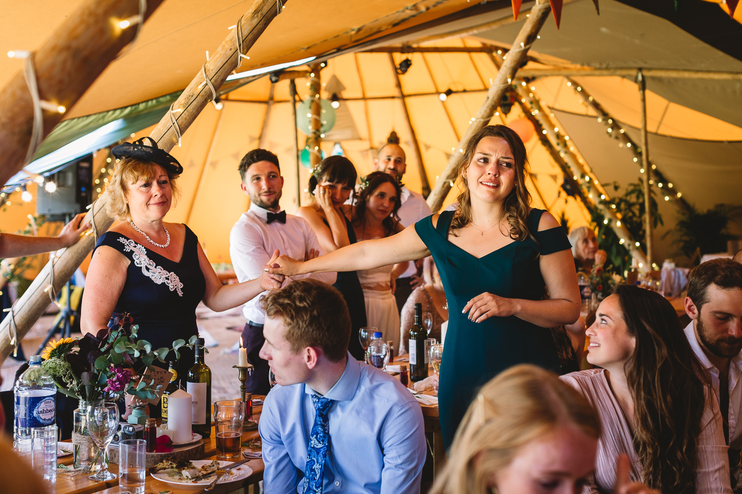 Photo at fun festival wedding inside of a Tipi, mother of groom and bridesmaid in tears holding hands during wedding speech with festival lights in background at alternative DIY wedding in Peterbourough