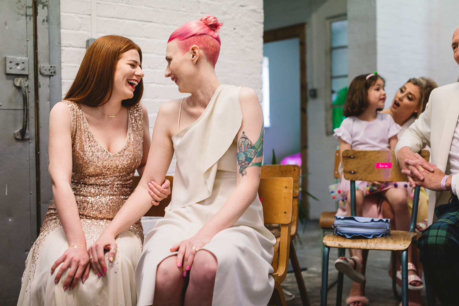 Photo in London of fun Same Sex wedding, two brides, one with pink hair and the other in gold sequin wedding dress are sitting together in a alternative wedding venue in Hackney. Arm in arm having fun laughing with each other.