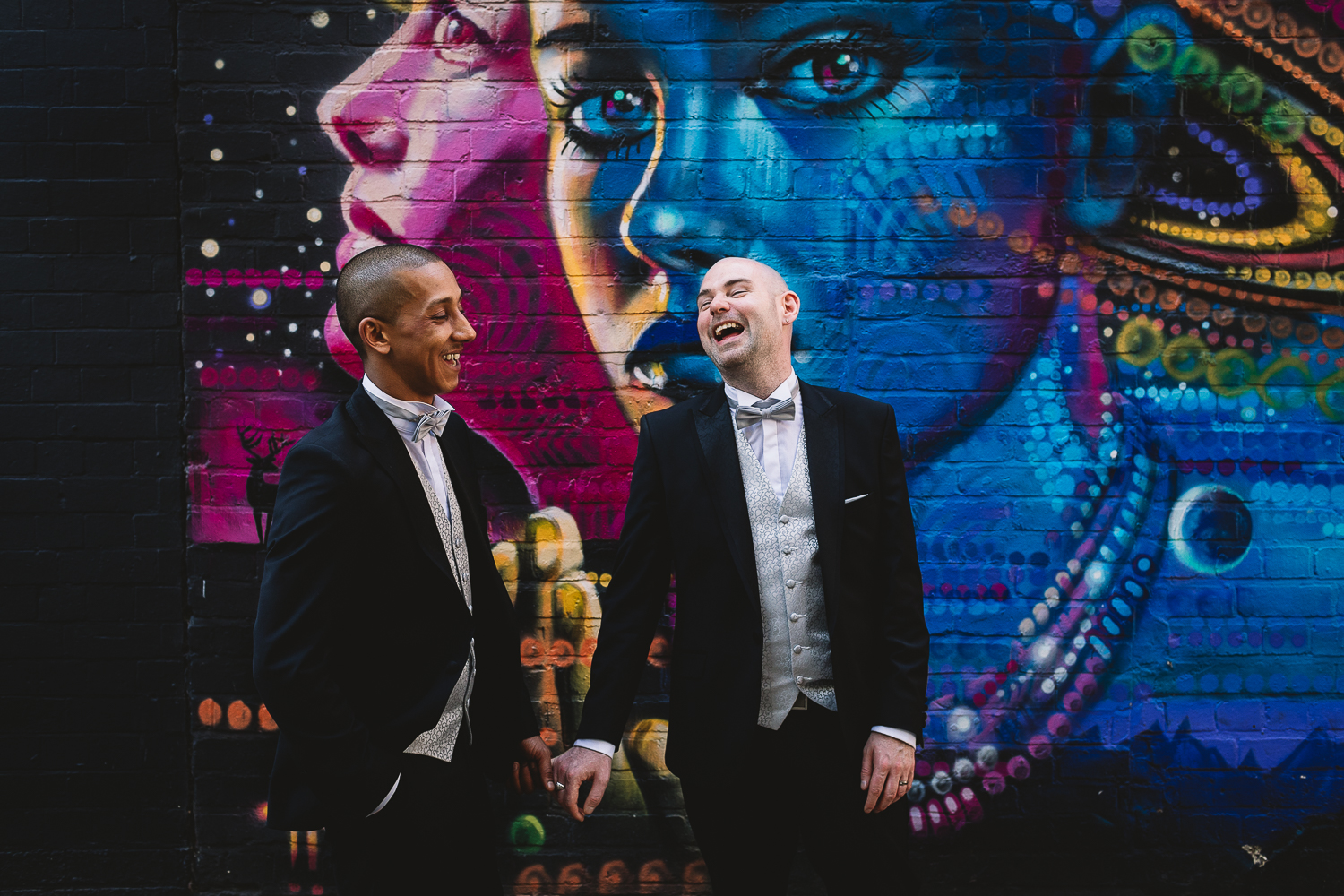 Photo of fun same sex wedding at the Bond Company in Digbeth. Two grooms in matching tuxes are holding hands and laughing in front of alternative colourful graffiti wall at the Custard Factory
