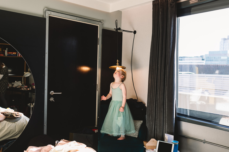 Flower girl in tulle skirt dress having fun with light