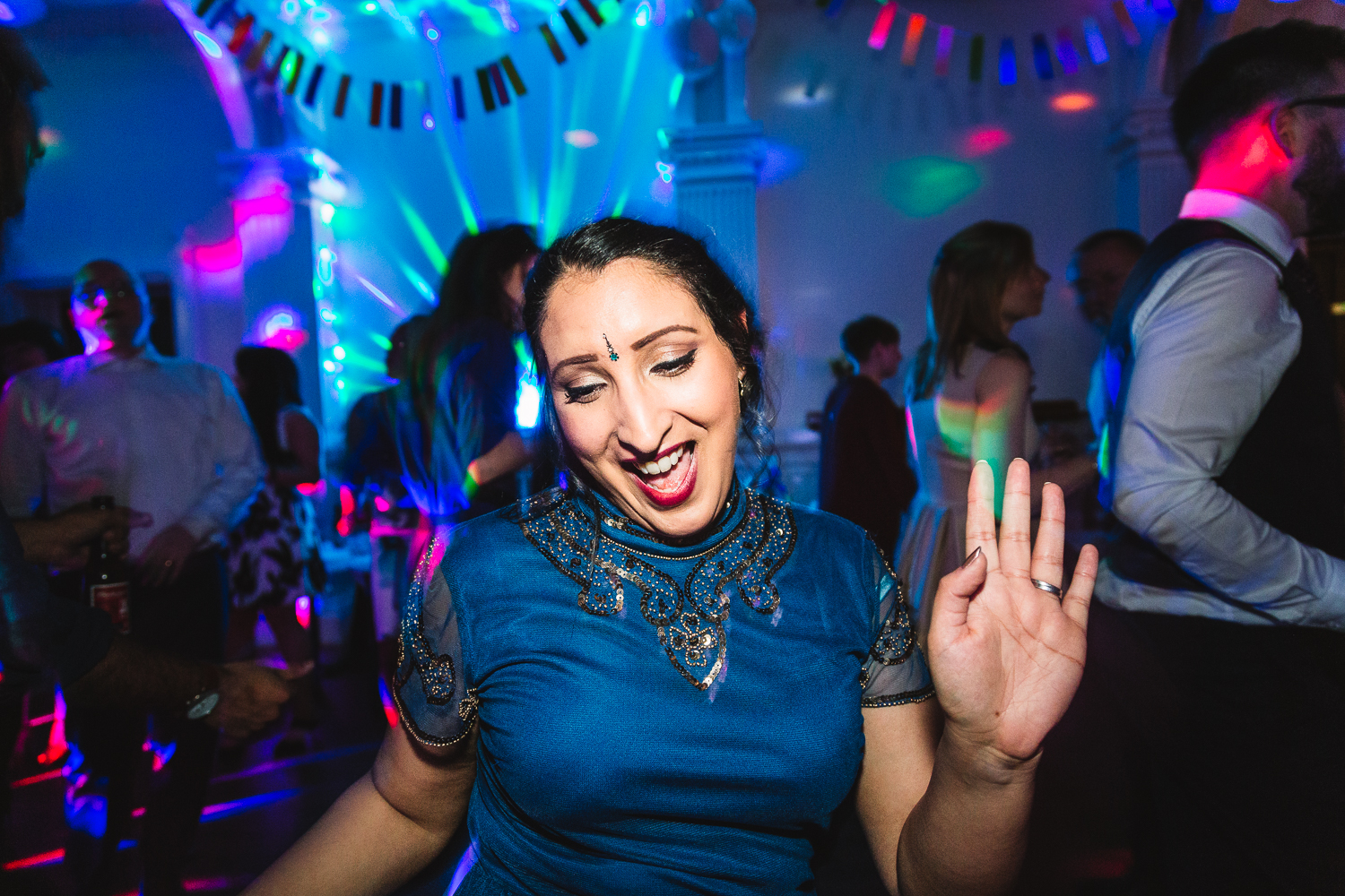 A photo of a woman in blue with a gem on her forehead having fun singing and dancing at a Worcestershire wedding