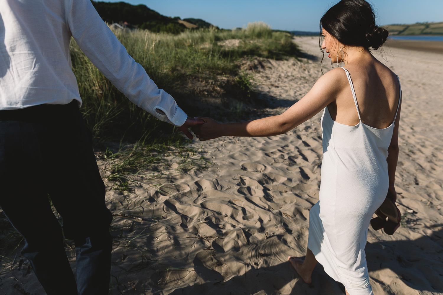 Bride and Groom in casual and simple wedding attire hand in hand walking along a sandy beach in Wales