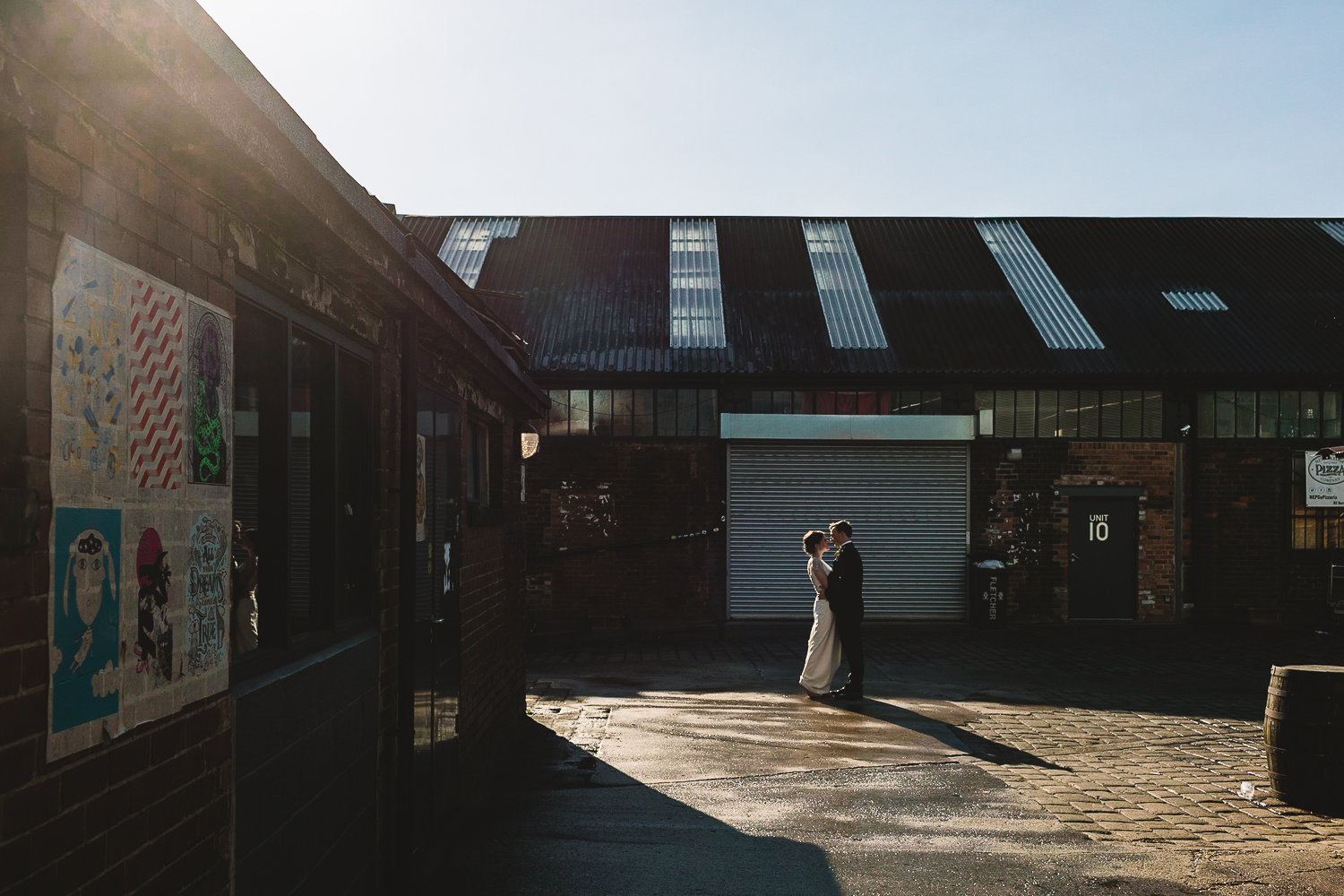 Bride and Groom stood facing each other in the sunlight in front of warehouses outside of 92 Burton Road Wedding Venue