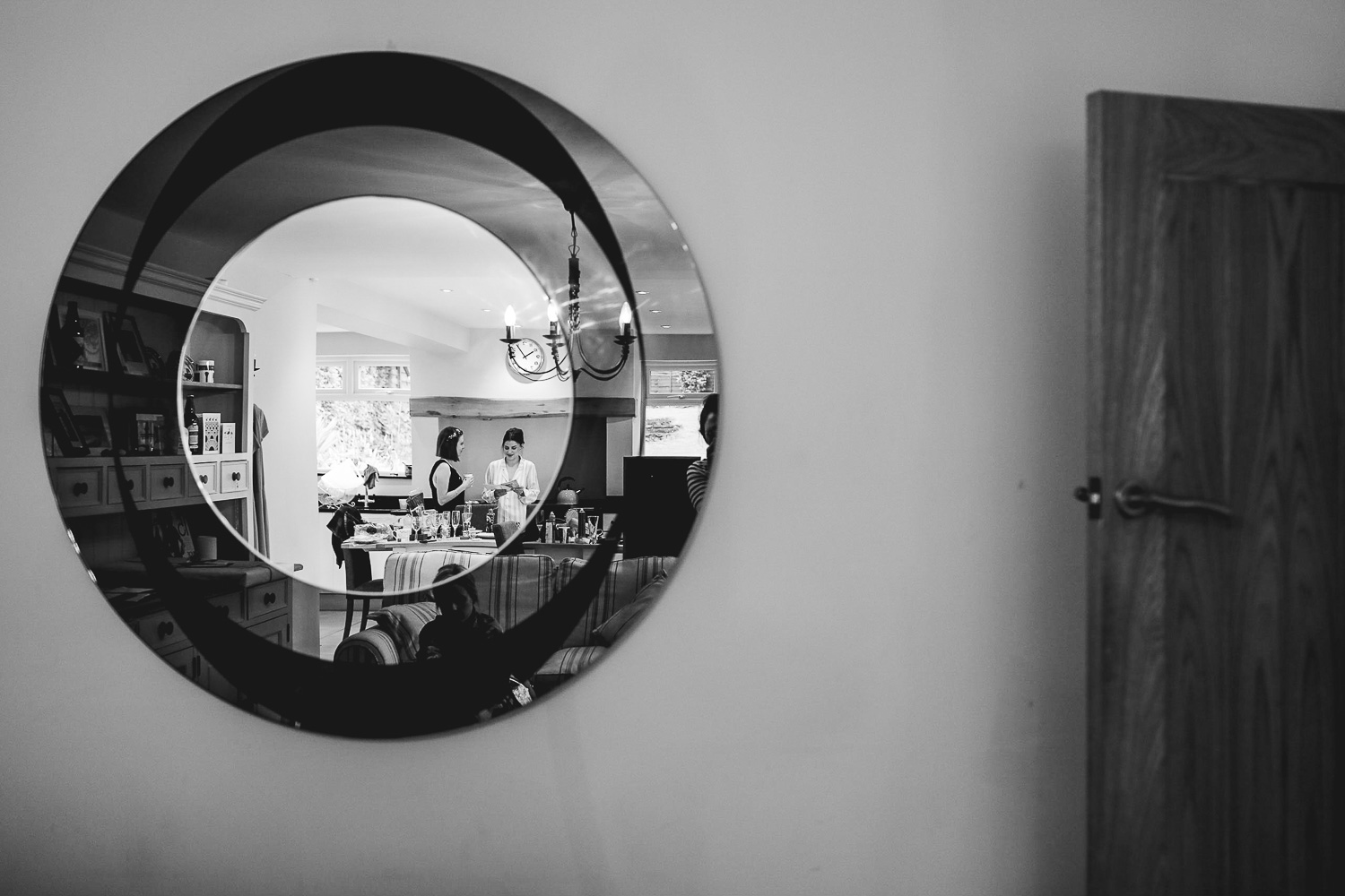 Documentary photograph of mirror where you can see the bride with a bridesmaid in pyjamas in the kitchen in the reflection at relaxed Sheffield wedding