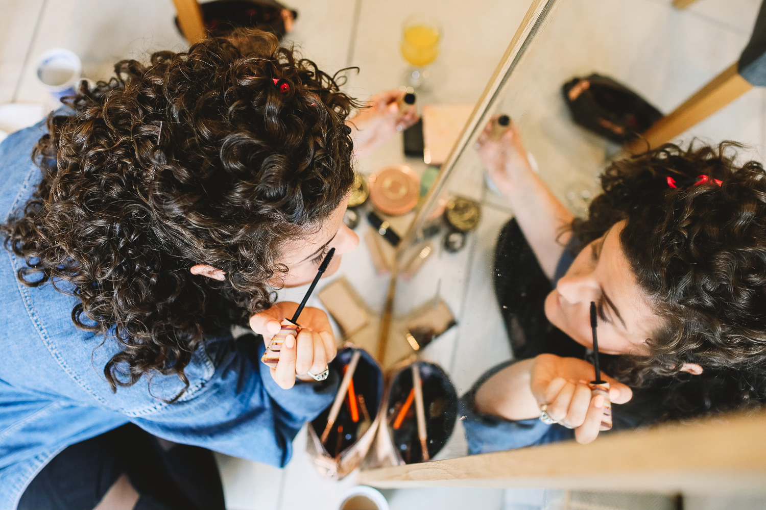 Photo of bridesmaid applying mascara in mirror at relaxed Sheffield wedding
