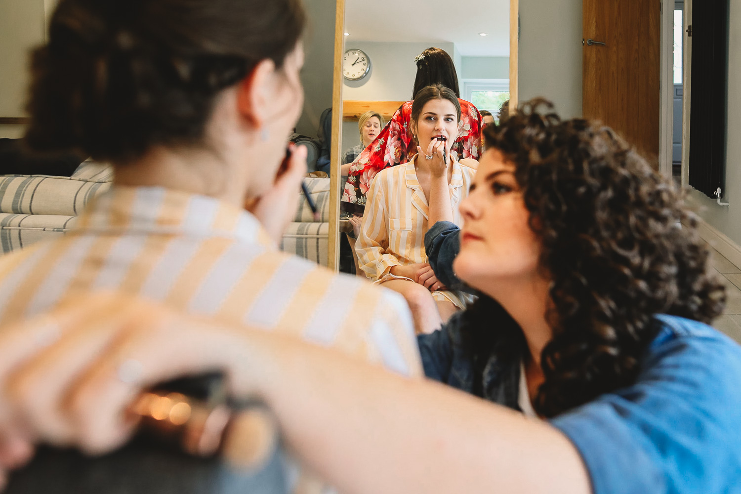 Bride in mirror having lipstick done by a friend during bridal prep in Sheffield