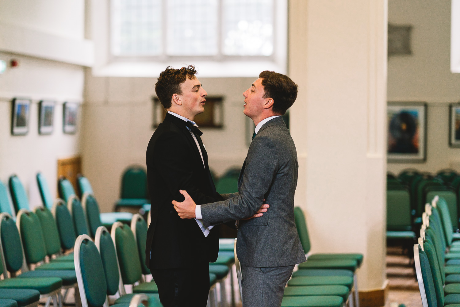 Photo inside of wedding venue of the Groom doing breathing exercises with one of his Groomsmen to calm the nerves before the wedding ceremony