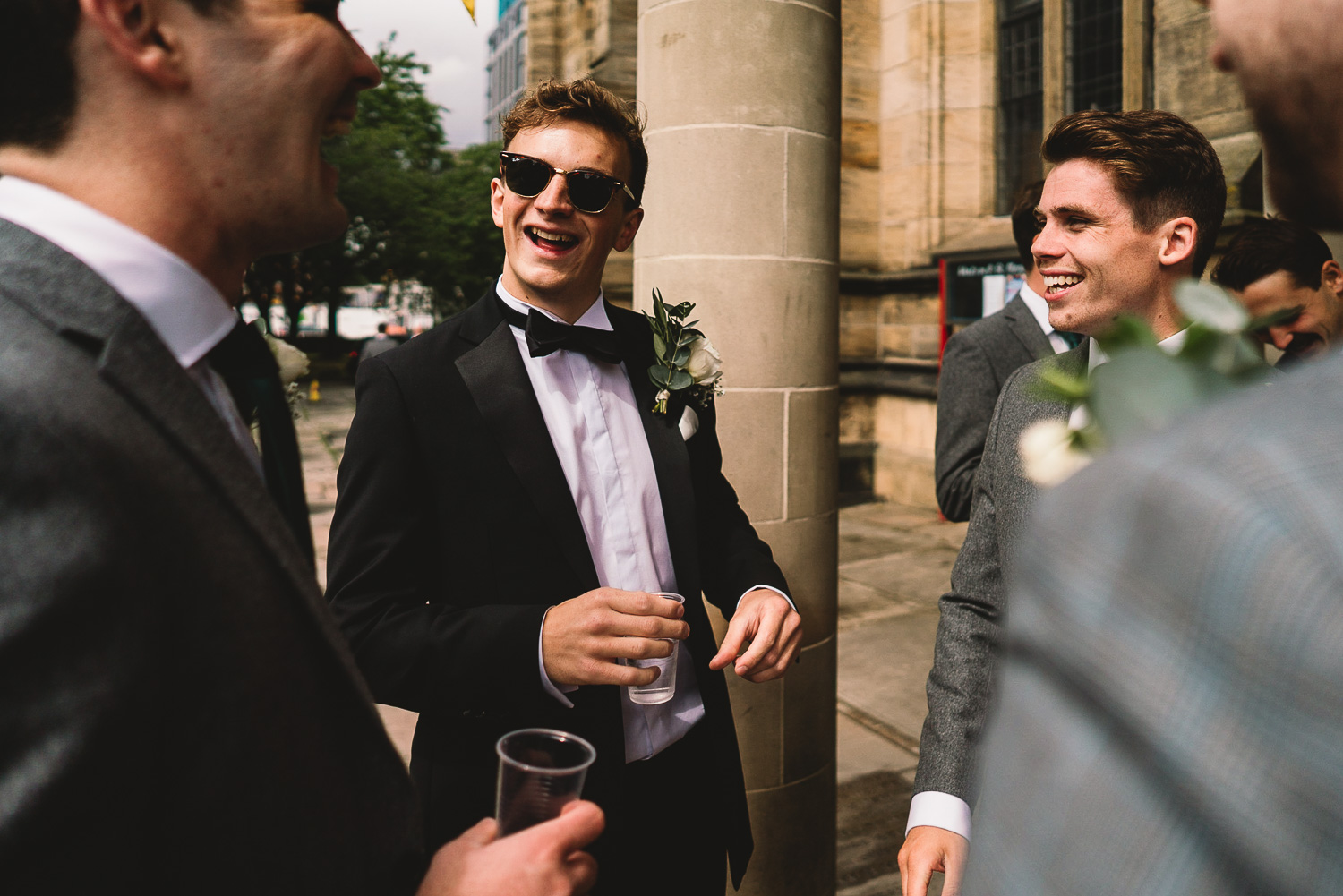 Groom in tux and sunglasses laughing and having fun with Groomsmen outside of Sheffield wedding venue before the ceremony in Sheffield