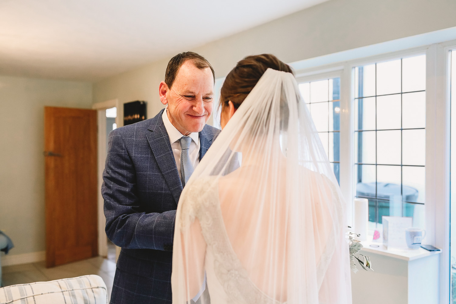 Dad approaches bride and holds her hands in his and has the happiest look on his face during bridal prep at relaxed Sheffield wedding