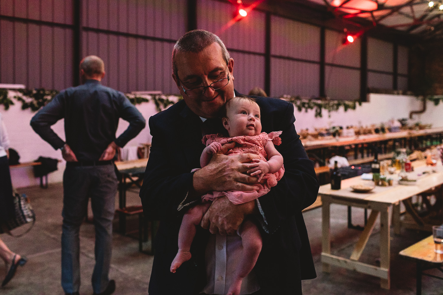 Man holding baby who is looking up at the colourful lighting in warehouse wedding venue 92 Burton Road in Sheffield