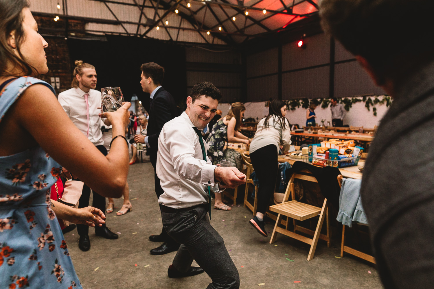 Guest dancing doing a pulling move to another guest on fun dance floor at alternative warehouse wedding venue 92 burton road