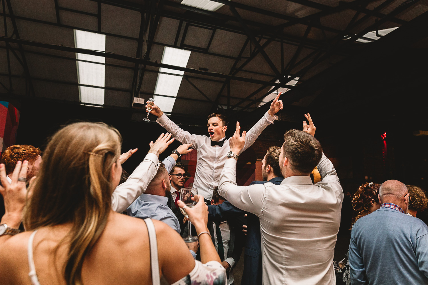 Photo shot from below of a groom on the shoulders of friends having fun with prosecco in one hand and arms in the air surrounded by friends in 92 Burton Road wedding venue in Sheffield