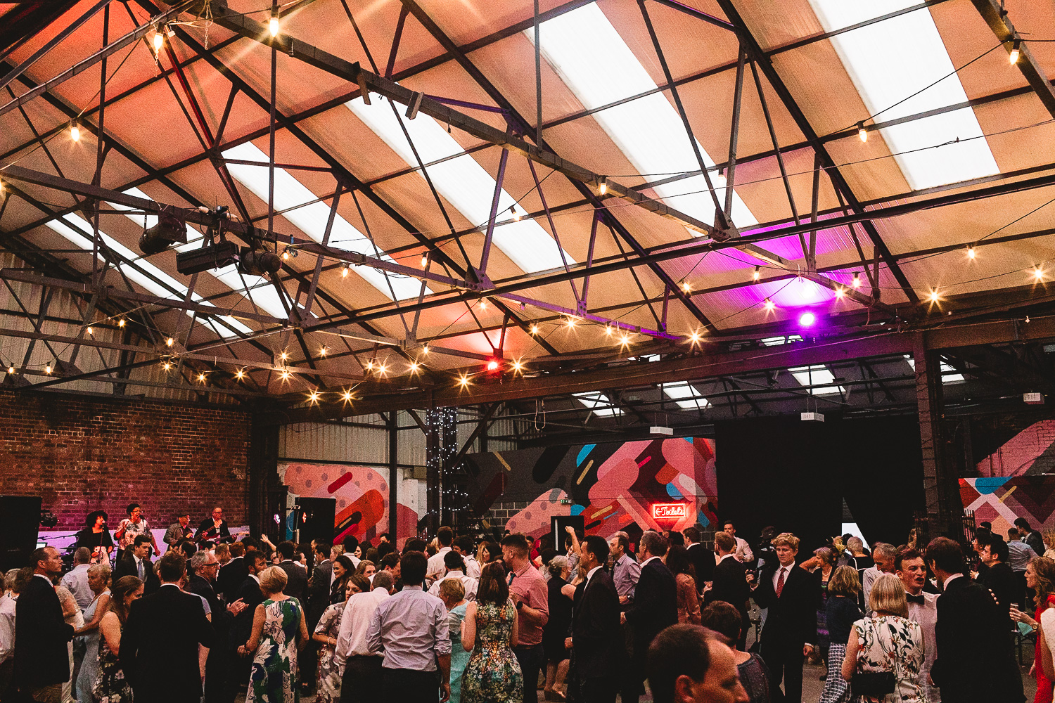 Wide photo of the dance floor flowing full of guests having fun dancing in warehouse wedding venue 92 Burton Road in Sheffield