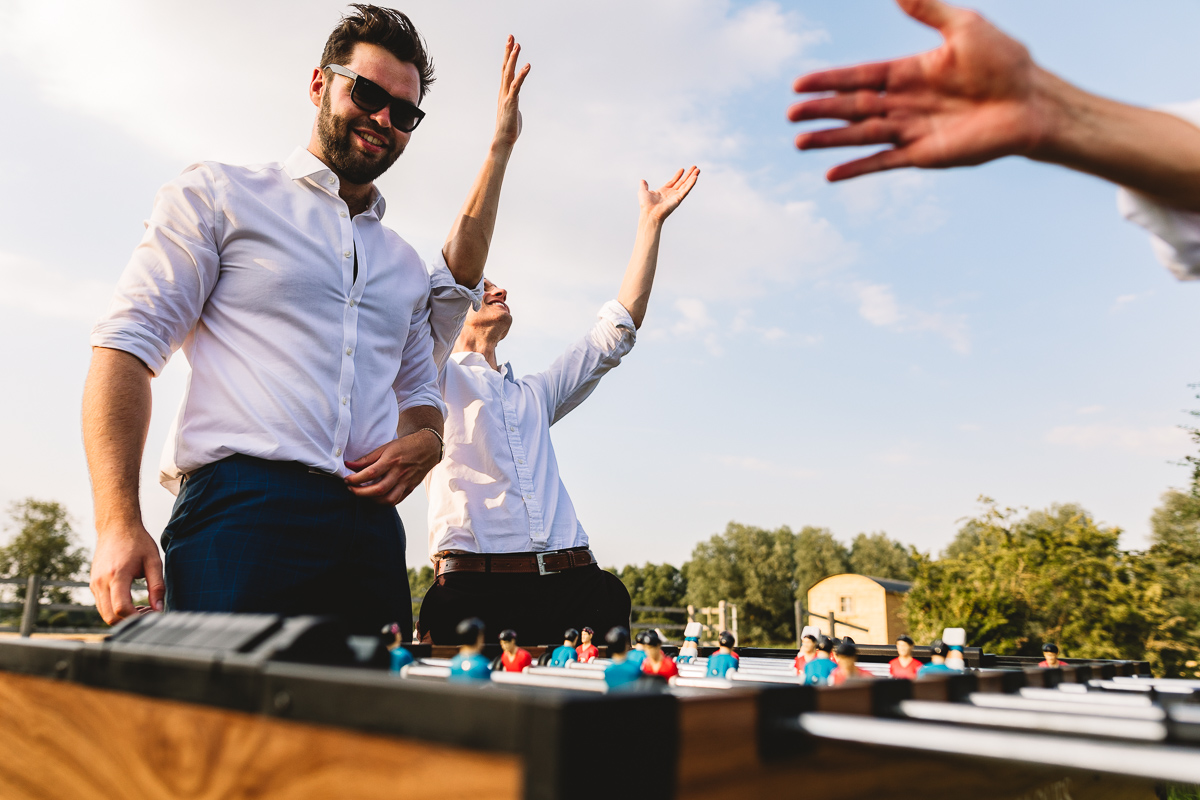 Photo of wedding guests playing table football outside at fun festival wedding at Berryfield Events in Peterbourough