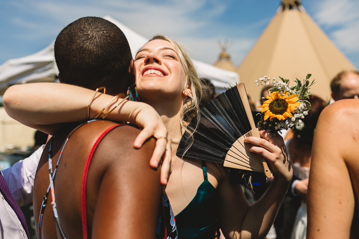 Close up natural photo of bridesmaid happily hugging a wedding guest outside of a tipi at festival wedding at Berryfields Events in Peterbourough